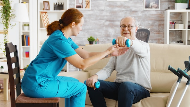 여성 간호사는 노인이 밝고 아늑한 은퇴 가정에서 아침 운동을 할 수 있도록 도와줍니다.