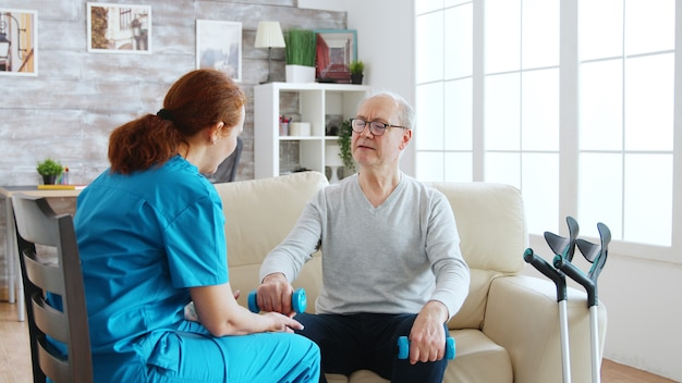 Female nurse helps an old man to make his morning exercises in bright and cozy retirement home