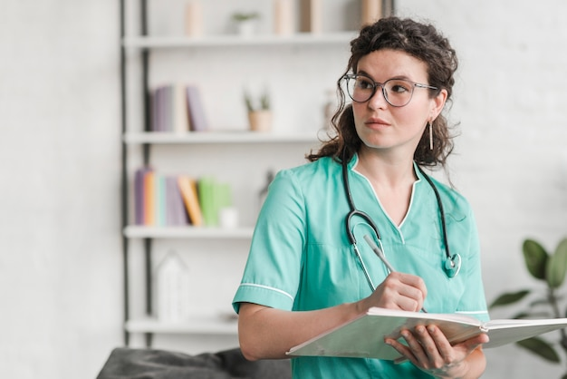 Female nurse holding book and pen wearing glasses looking away