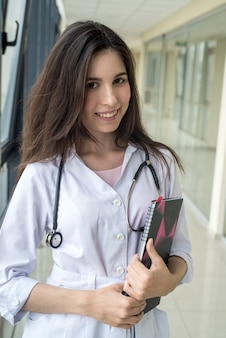 ノートに患者の病歴を保持し、病院の近代的な廊下で一人で立っている女性看護師