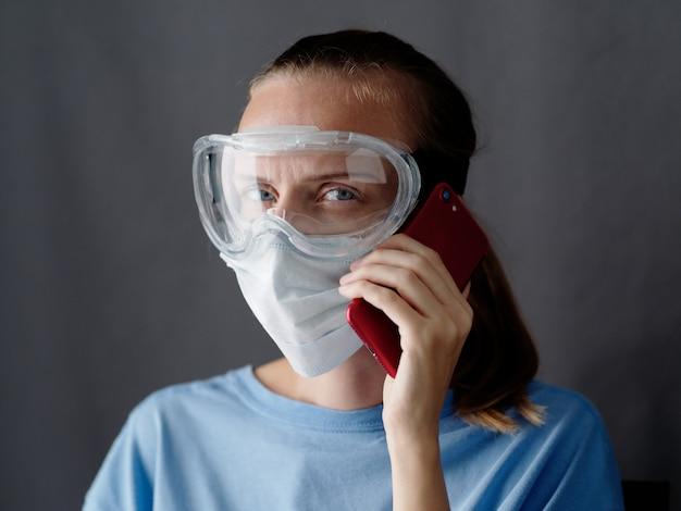 マスクをした女性看護師が灰色の背景にスマートフォンを使用し、女性医師が携帯電話を持っています。