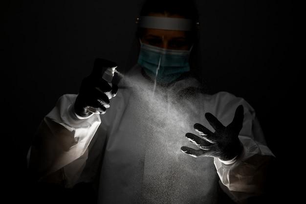 医療用防護服の女性看護師が手に消毒剤をスプレーします。