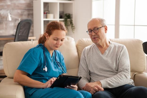Медсестра в доме престарелых помогает старику использовать планшетный компьютер.