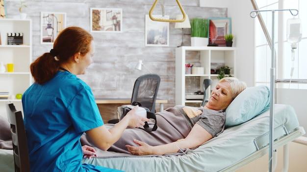 老人ホームの女性看護師が、病院のベッドに横たわっている間、痛みを和らげ、気を散らすために、障害のある老婦人にvrヘッドセットを提供します