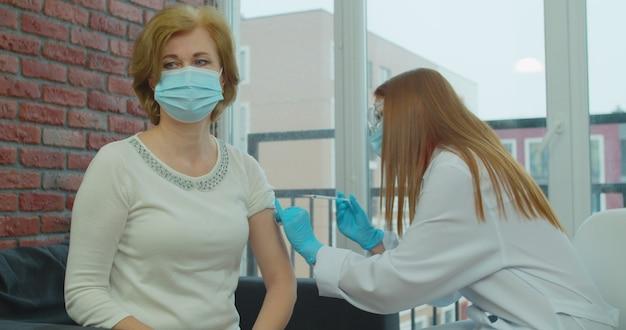 수석 남성 환자를 주입하는 제복을 입은 여성 간호사. covid-19 감염에 대한 예방 접종을 주사하는 젊은 의사.