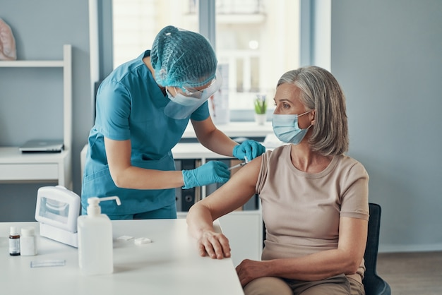Медсестра делает инъекцию зрелой женщине во время работы в больнице