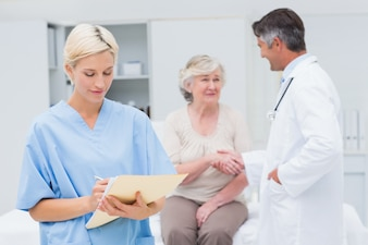 Female nurse making reports while doctor and patient shaking hands