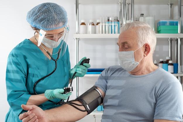 病院で成人男性の血圧を測定する女性看護師