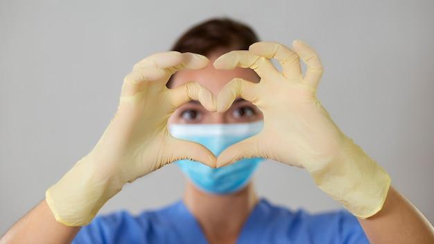 女性の看護師または医師が彼女の指と手でラテックス手袋で彼女の目の前にハートを形成します。