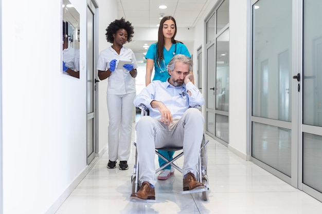 휠체어에 병원에서 퇴원하는 노인 남성 환자를 밀고 여성 간호사
