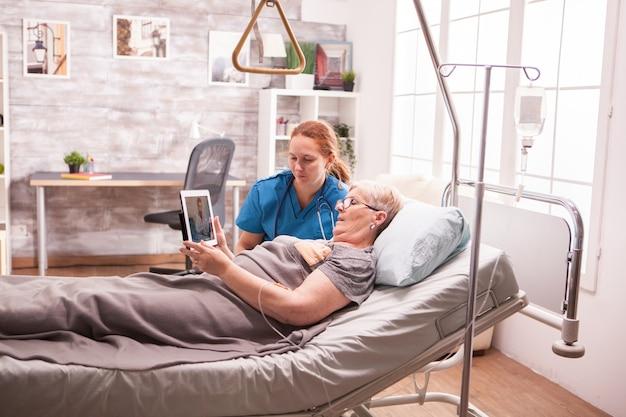 ナーシングホームで年配の女性に医療報告を示す女性看護師。
