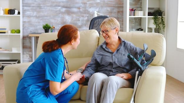 ナーシングホームでアルツハイマー病の老婆と話している女性看護師