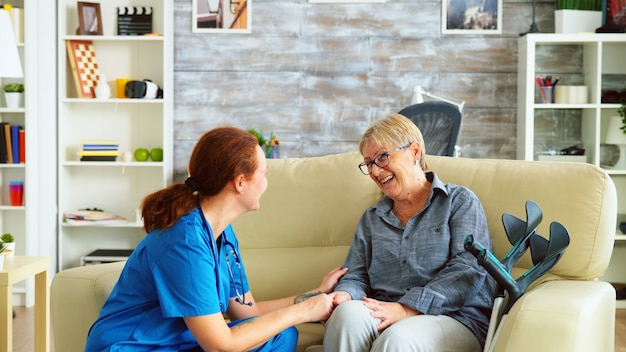 Female nurse talking with old woman with alzheimer in nursing home