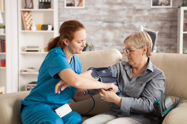 ナーシングホームの年配の女性にデジタル血圧計を使用している女性看護師。