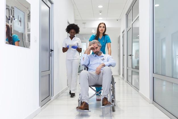 Female nurse wearing scrubs wheeling patient in wheelchair through lobby of modern hospital