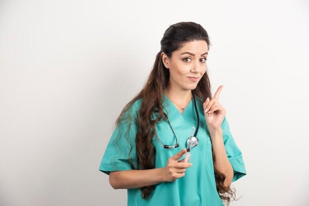 Infermiera femminile con l'iniezione della tenuta dello stetoscopio.