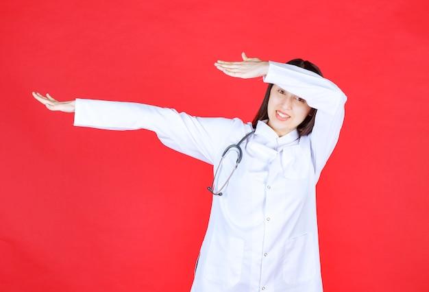 청진기를 가진 여성 간호사가 무서워하고 무언가를 멈추려 고합니다.