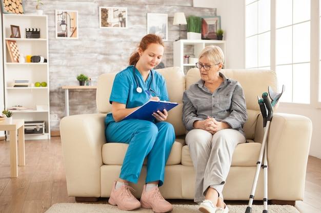 여성 간호사는 요양원에서 수석 여성과 이야기하면서 클립보드에 글을 쓰고 있습니다.