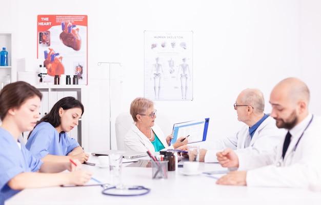 의료 전문가가 병원 회의실에서 바이러스성 질병에 대해 설명하는 동안 메모를 하는 여성 간호사. 질병에 대해 동료와 이야기하는 클리닉 전문 치료사, 의학 전문가