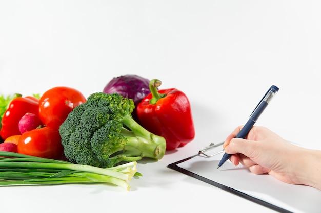 野菜ダイエット計画を書いている女性栄養士の医者。白い背景で隔離の有機栄養成分