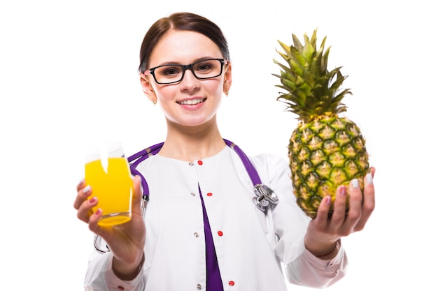 Female nutritionist hold pineapple and glass of fresh juice in her hands on white background