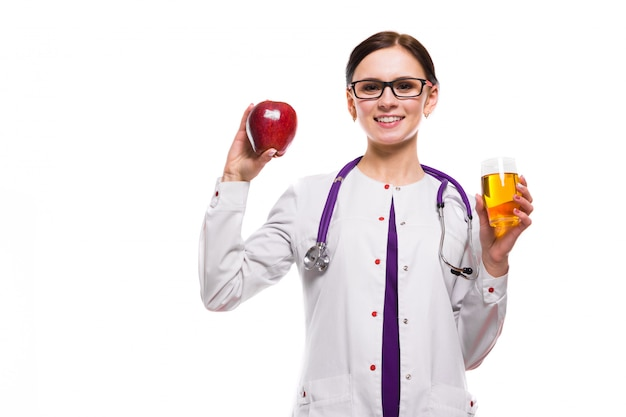 Female nutritionist holding apple and glass of fresh juice in her hands on white