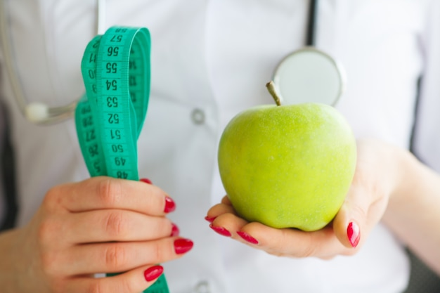 Female nutritionist and holding an apple and a measure tape. new start for healthy nutrition, body slimming, weight loss. cares about body