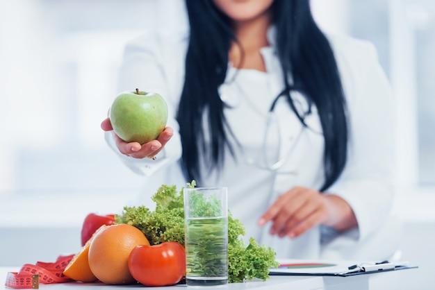 リンゴを手に持っている白衣の女性栄養士。