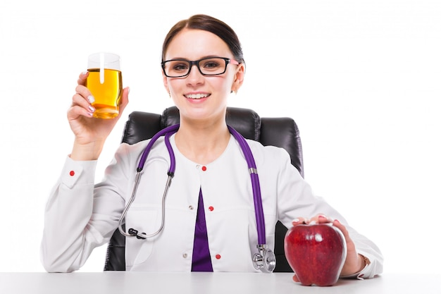 Female nutritionist sitting in her working place showing and offering glass of apple fresh juice holding apple in her hand on white