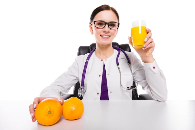 Female nutritionist sitting in her working place showing and offering glass of orange fresh juice holding orange in her hand