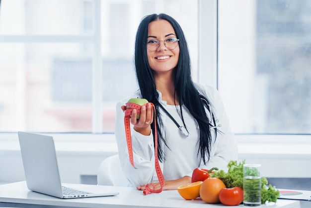 Female nutritionist in white coat holding apple with measuring tape.