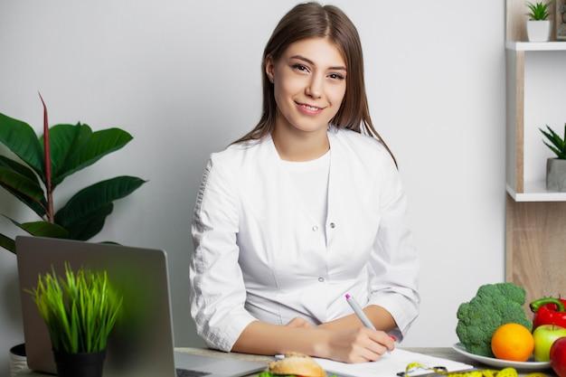 그녀의 책상에서 일하는 과일과 여성 영양사