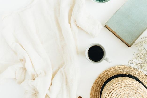 Женский офисный стол с кофе, книгой, соломенной шляпой, цветами и одеялом на белой поверхности