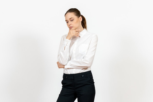 Female office employee in elegant white blouse with thinking face on white