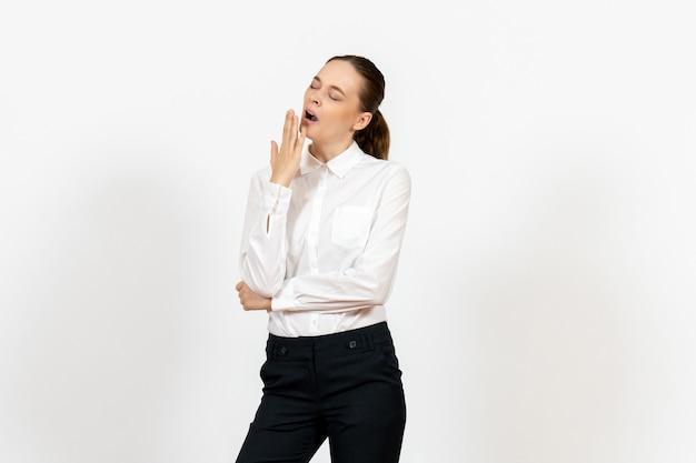 Female office employee in elegant white blouse yawning on white