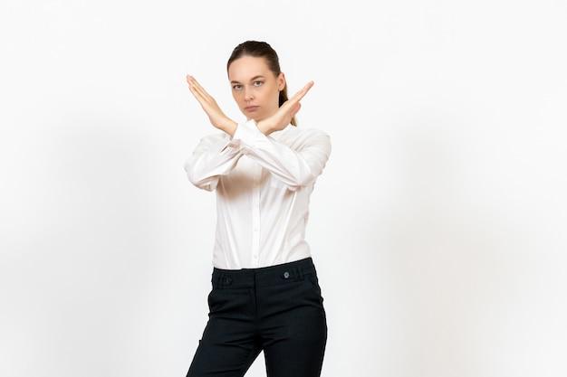 Офисный служащий в элегантной белой блузке, показывая знак запрета на белом