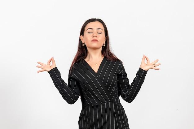 白地に瞑想ポーズで厳格な黒のスーツを着た女性のサラリーマン