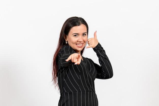 白を指す厳格な黒のスーツの女性のサラリーマン