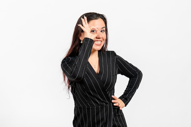 明るい白でポーズをとる厳格な黒のスーツの女性オフィス従業員