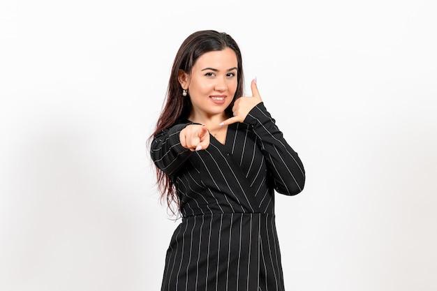 Офисный служащий в строгом черном костюме улыбается и показывает на белый