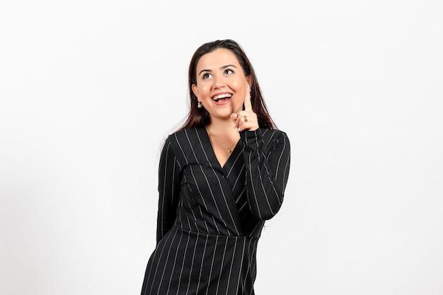 白に笑みを浮かべて厳格な黒のスーツを着た女性のサラリーマン