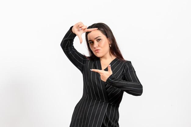 白地に撮影ポーズをとる厳格な黒のスーツの女性事務員