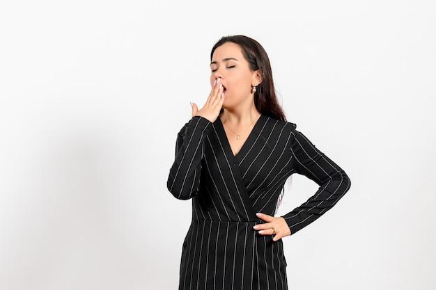 白をあくびする厳格な黒のスーツの女性のサラリーマン