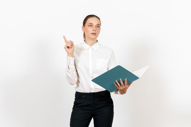 白の青いファイルを保持し、読んで白いブラウスの女性のサラリーマン