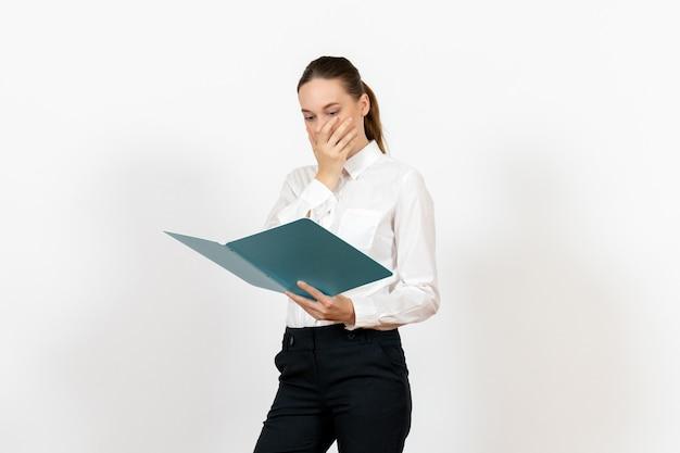 흰 블라우스를 들고 흰색에 파란색 파일을 읽는 여성 사무실 직원