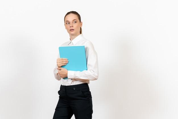 白地に青いファイルを保持している白いブラウスの女性事務員