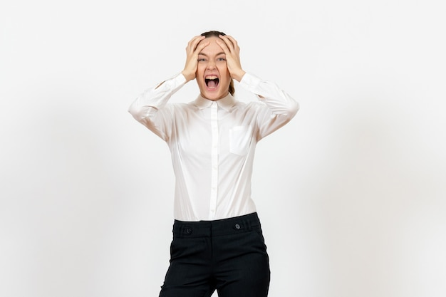 Impiegato femminile di ufficio che grida in camicetta bianca su bianco