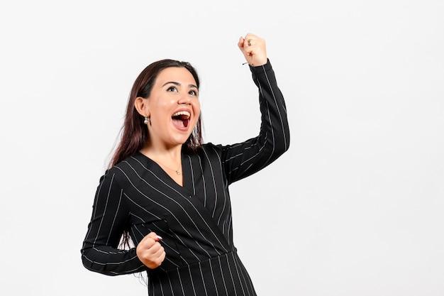 Impiegato femminile dell'ufficio in vestito nero rigoroso che si rallegra emotivamente su bianco