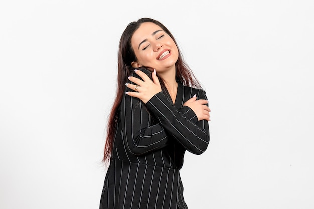 Female office employee in strict black suit hugging herself on white