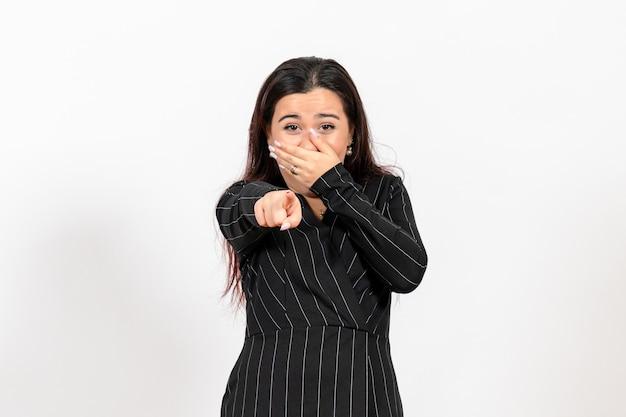 Impiegato femminile in abito nero rigoroso ridendo su bianco